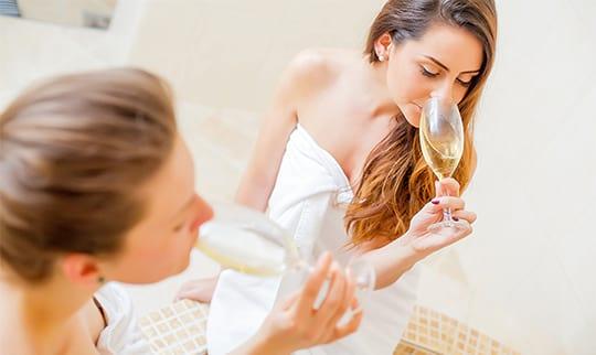Zwei junge Frauen in weißen Bademänteln trinken ein Glas Sekt