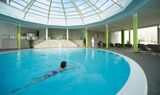 Frau schwimmt im Pool unter großer Dachkuppel