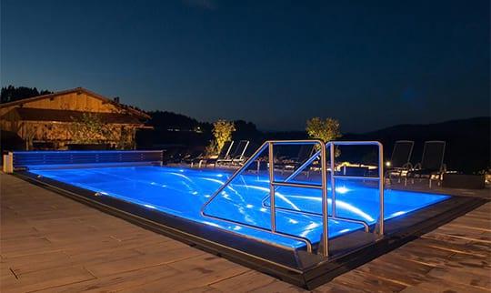 Blau beleuchteter Aussenpool am Abend mit Aussicht
