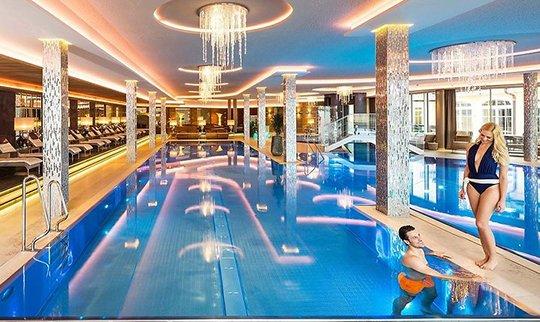 Mann und Frau stehen in und am Pool