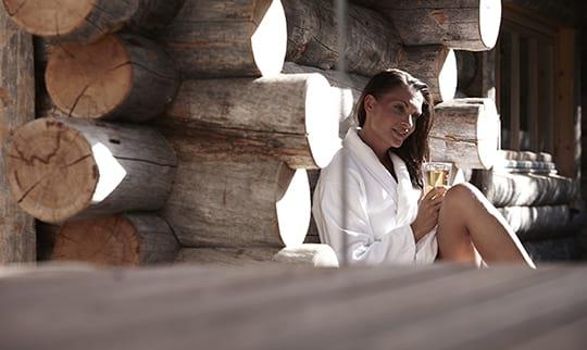 Frau in weißsen Bademantel vor der Außensauna
