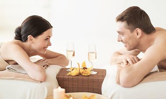 Mann und Frau entspannen auf Liegen neben zwei Sektgläsern