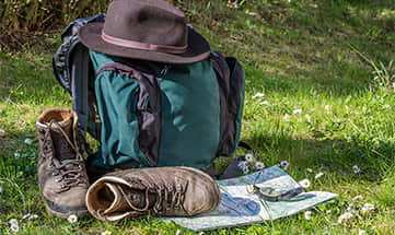 Wanderstiefel, Wanderkarte, Hut und Rucksack auf einer Wiese