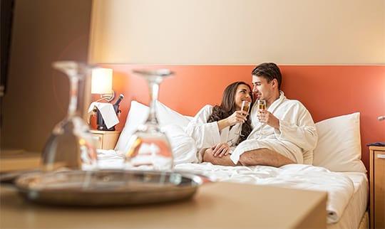 Ein Paar entspannt in weißen Bademänteln auf einem Bett